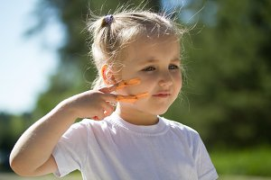 Cute little girl draws lines on the face with finger paints at summer vacation in park, horizontal