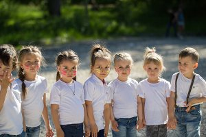 Group of little children in white t-shirts with painted faces lined up in line in summer day