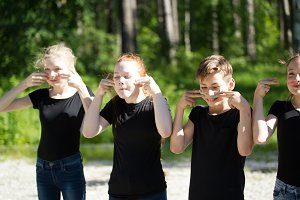 Group of teenagers in black t-shirts painting their faces having fun outdoors at sunny day