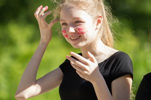 Portrait of happy teenager girl with painted face having fun outdoors at sunny day