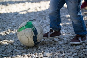 Legs of toddler boy kicks a soccer ball outdoors at sunny day