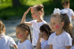 Caucasian little girls team with painted faces playing in summer park