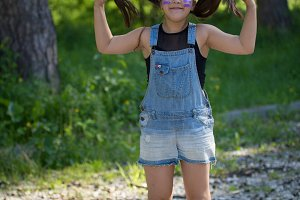 Cheerful teenager girl with long hair having fun in the park at sunny day