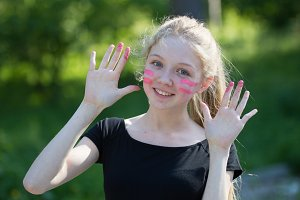 Portrait of funny teen girl smiling with finger paints on her face in summer park