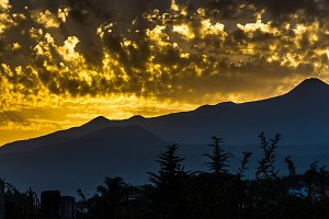 A beautiful sunset in the mountains in the gold clouds