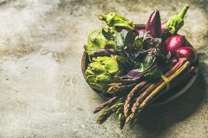 Flat-lay of green and purple vegetables on plate, concrete background