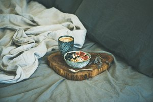 Rice coconut porridge and cup of espresso in bed