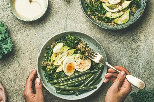Quinoa, kale, green beans, avocado, egg bowls in female hands