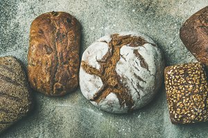 Top view of bread loaves over grey concrete background