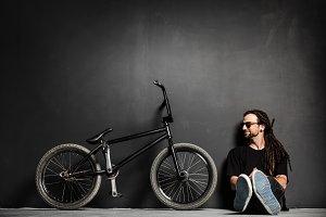 Young smiling man sitting next to his BMX bike.