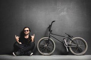 Happy man sitting next to his BMX bike, showing rocker gesture.