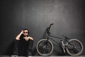 Man sitting next to his BMX bike, adjusting his sunglasses.