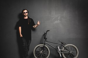 Man standing next to his BMX bike, pointing his finger.