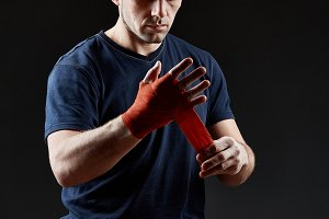 Low key studio portrait of handsome muscular fighter preparing for boxing on dark blurred background
