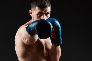 Low key studio portrait of handsome muscular fighter practicing boxing on dark blurred background