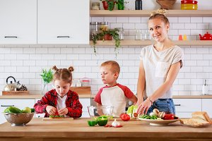 Picture of young mother with daughter and son cutting vegetables at table