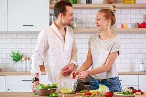 Photo of beautiful man and woman cooking vegetables in the kitchen