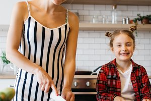 Photo of beautiful woman with her daughter cutting vegetables in kitchen