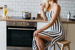 Photo of beautiful woman in long striped dress in kitchen