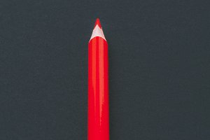 Red pencil on black background
