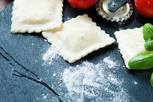 Uncooked ravioli with tomato and bas