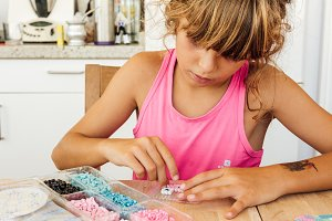 girl playing a board game at the kitchen table