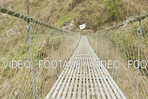 Suspension bridge over the river in mountains in Nepal. Manaslu circuit trek.