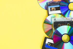 CD disks and audio cassettes on a yellow pastel background. Minimalism.