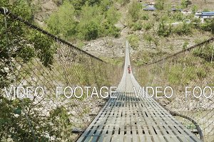 Local kids run and play on the suspension bridge over the river in Nepal.