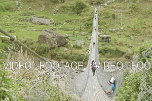 Backpackers walk on suspension bridge over river in Nepal. Manaslu circuit trek.