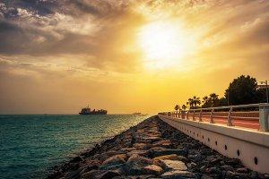 Cargo container ship leaving Dubai Marina at sunset