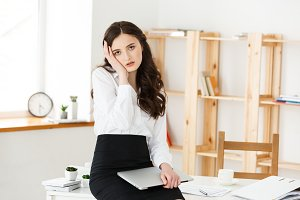 Tired young businesswoman suffering from long time sitting at computer desk in office