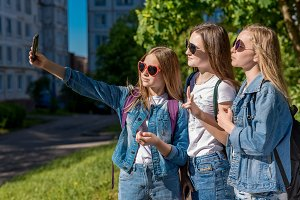 Three girls girlfriend. Summer in nature. In his hands holds a smartphone. Makes photos on phone. The concept of school friends. In denim clothing, white T-shirts.