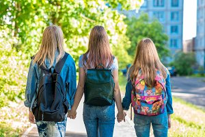 Three teenage girls. They hold each other's hands. Returns home after school. Summer in nature. Behind backpacks. Back view. The concept of school girlfriends.