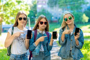 Three teenage girls. Summer in nature. In his hands holds a smartphone. Sunglasses. In denim suits. A gesture of hands points to the phone. The concept is a new application.