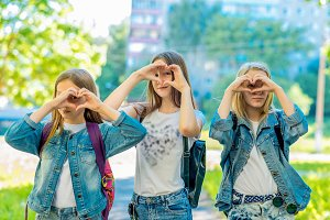 Three girls schoolgirl. Summer in nature. With a gesture of the hand, heart is shown. Smiles happily. Rest after school. The concept of friendly love.