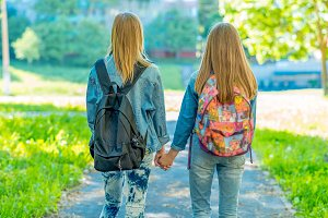 For a teenage girl. Summer nature. Returns home after school. They hold each other's hand. Back view. Behind backpacks. 2 sisters go home