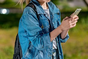 A teenage girl is holding a smartphone. Summer in nature after school. Dressed in denim clothing behind her backpack. Writes the message to parents.