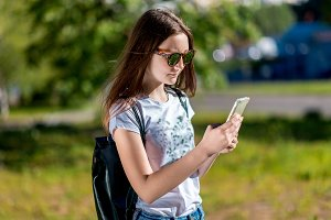 Girl schoolgirl. Holds the hands of the phone. Summer in nature. After school Camping. Behind the backpack. Writes a message on the Internet On Smartphone