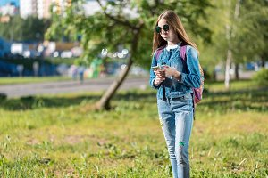Girl schoolgirl. Summer in nature. In hands smartphone. She is wearing jeans clothes. Behind backpack. Free space for text. The concept communication on Internet. Writes messages social networks.