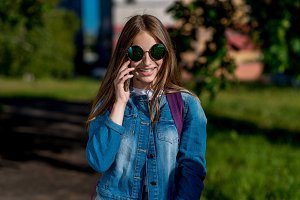 A teenage girl. In the summer after school. In his hands holds a smartphone. He talks on phone. Happy smiling. In a jeans sweater sunglasses.