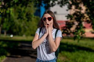 Girl schoolgirl. Summer in nature. In a T-shirt, behind a backpack. In red Sunglasses in form of heart. The concept of surprise gift. Emotions of happiness are unexpected joy, horror, accident.