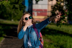 Girl schoolgirl denim jacket, backpack sunglasses. Summer in nature. She covers mouth with palm. Finger points to side. The concept surprise is horror of accident. Emotions of fear misunderstanding.