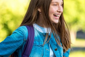 Girl schoolgirl. Summer in nature. In denim jacket behind a backpack. Happy smiling returns home. Joyful laughs after a joke. Emotion of delight and delight.