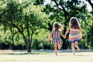 Two little girls running in the park, holding hands.