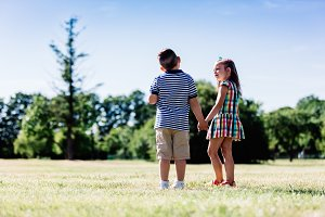 Little boy and girl holding hands in the park.