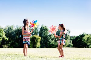 Two little girls blowing upon colorful pinwheels.