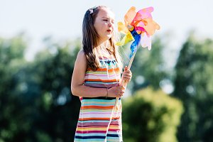 Little girl blowing upon a pinwheel in the park.