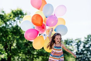 Happy girl in running with a bunch of balloons