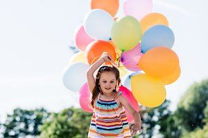Happy little girl running with a bunch of colorful balloons
